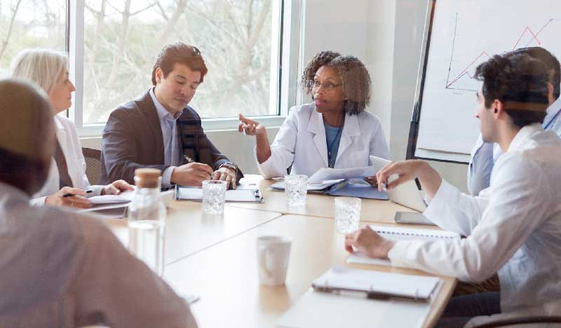 Group of healthcare providers sitting at meeting table
