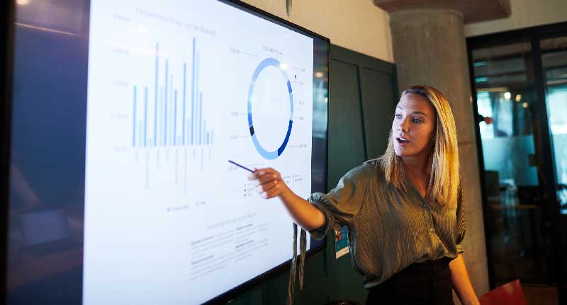 Woman presenting with data charts on screen