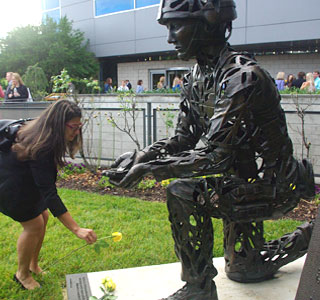 Macey Henderson places a rose on the UNOS Fallen Soldier Memorial (Photo: UNOS)