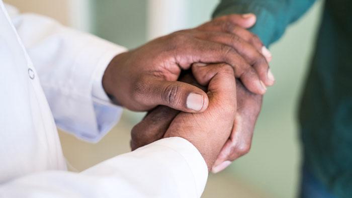 Doctors hands holding patient's hand