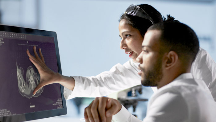 Two people reviewing imaging study on monitor