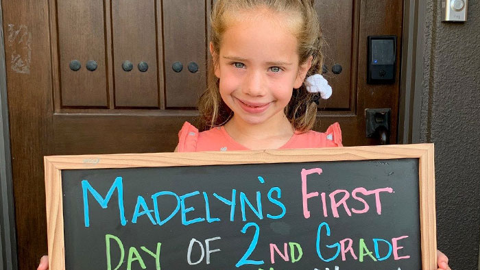 Madelyn, pediatric heart transplant recipient, holding chalkboard sign announcing her first day of 2nd grade